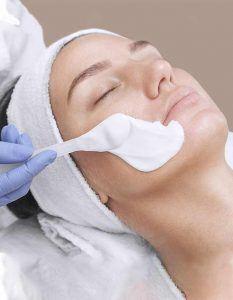 photo of a woman receiving a hydra cloud facial mask